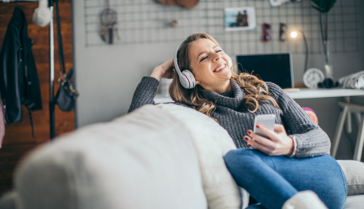 A lady sitting on the couch with earphones on