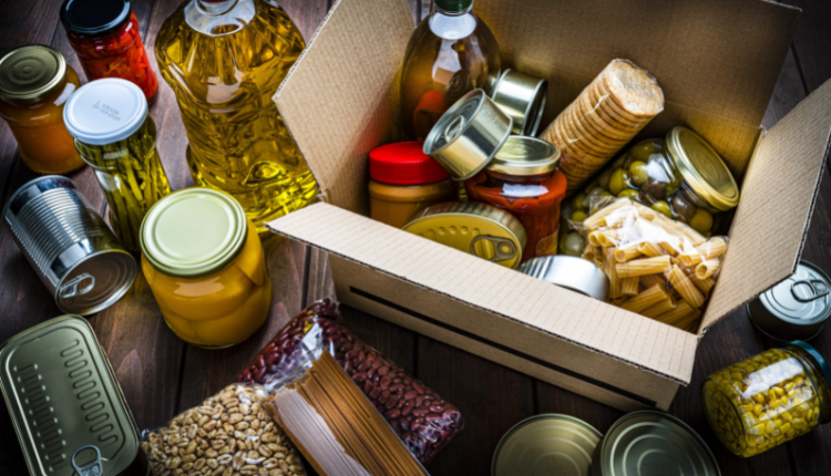 Tins and jars of food in a cardboard box