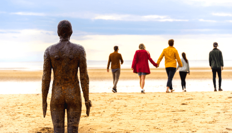 A bronze statue with people walking in front towards the beach