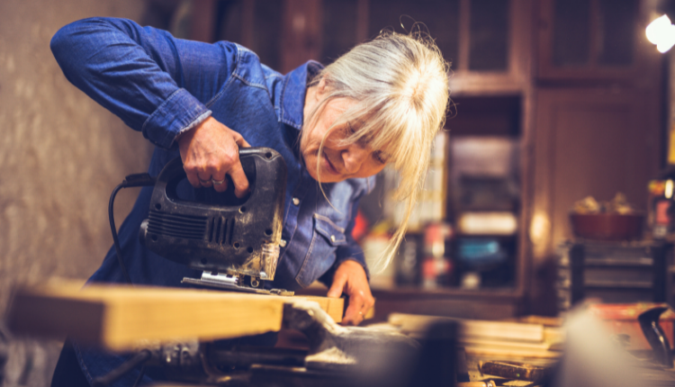 A lady working on a piece of wood in a workshop