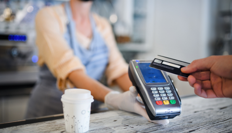A person taps a debit card onto a card machine with a coffee in front of them