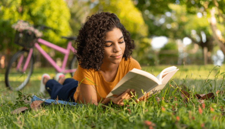Lady reading a book on the grass