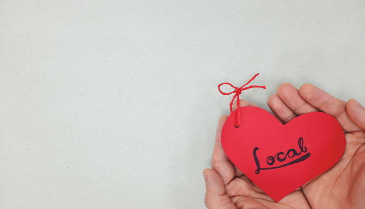 A little red heart with 'love' written on it, held in two hands.