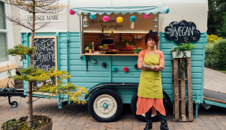 A lady stands outside a colourful food truck wearing a green apron.