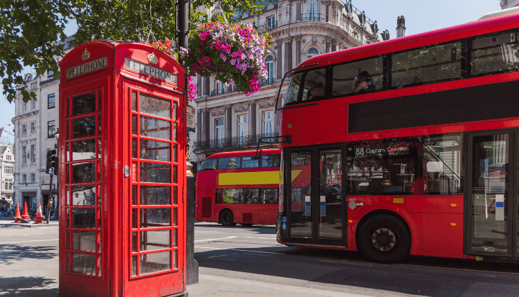 Two red double decker buses pass eachother on a busy street in London